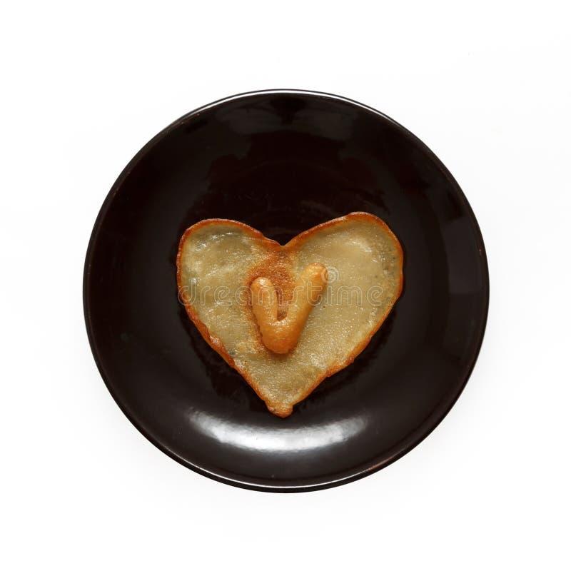 Herz formte Pfannkuchen mit Innere des Buchstaben V auf der dunkelbraunen Platte, die auf weißem Hintergrund lokalisiert wurde stockbild