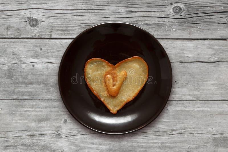 Herz formte Pfannkuchen mit Innere des Buchstaben V auf dunkelbrauner Platte auf hölzernem Hintergrund lizenzfreie stockfotografie