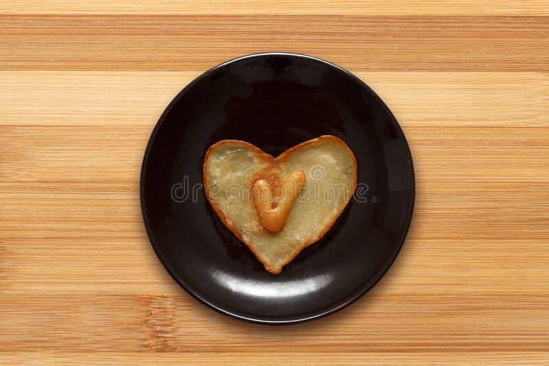 Herz formte Pfannkuchen mit Innere des Buchstaben V auf dunkelbrauner Platte auf hölzernem Hintergrund stockbild