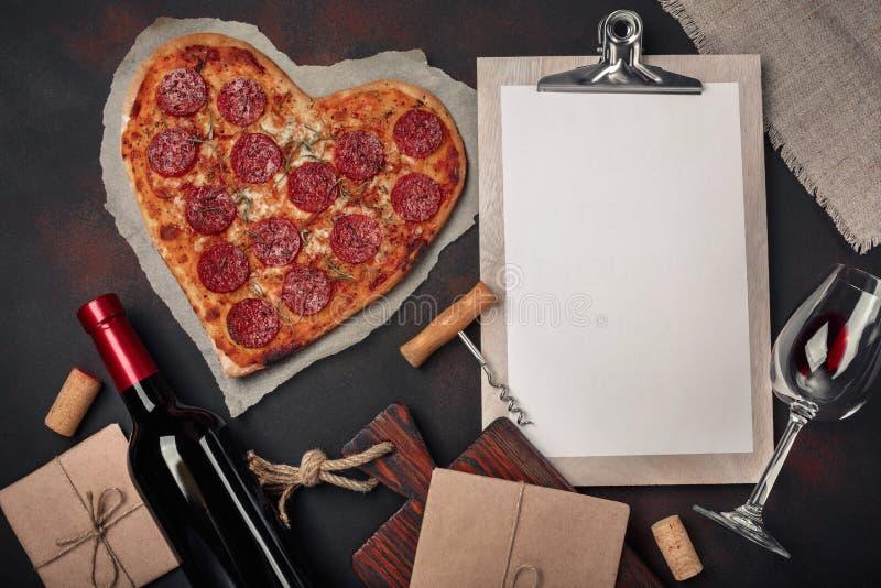 Herz formte Pizza mit dem Mozzarella, sausagered, Weinflasche, Korkenzieher und Tablette auf rostigem Hintergrund lizenzfreie stockbilder