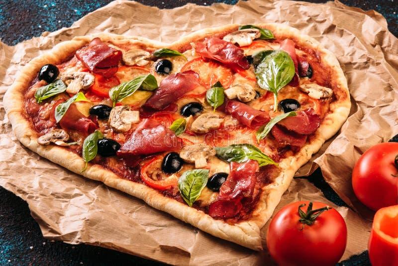 Herz formte Pizza mit Tomaten und Prosciutto für Valentinsgruß-Tag auf Weinleseschwarz-Türkishintergrund Chef gießt Olivenöl über stockbild