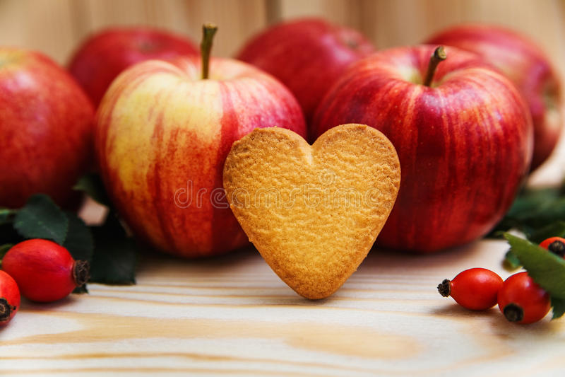 Herz formte Plätzchen auf dem roten Apfelhintergrund mit Beeren n lizenzfreie stockfotografie