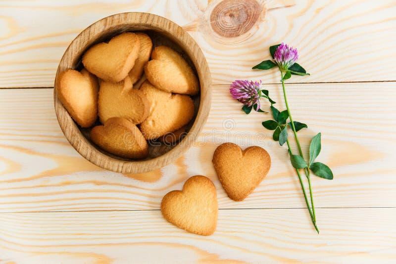 Herz formte Plätzchen, Blumen auf Holztischhintergrund Beschneidungspfad eingeschlossen lizenzfreie stockbilder