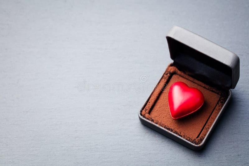 Herz formte Praline in einer Geschenkbox auf Schieferhintergrund Beschneidungspfad eingeschlossen Kopieren Sie Platz lizenzfreie stockbilder