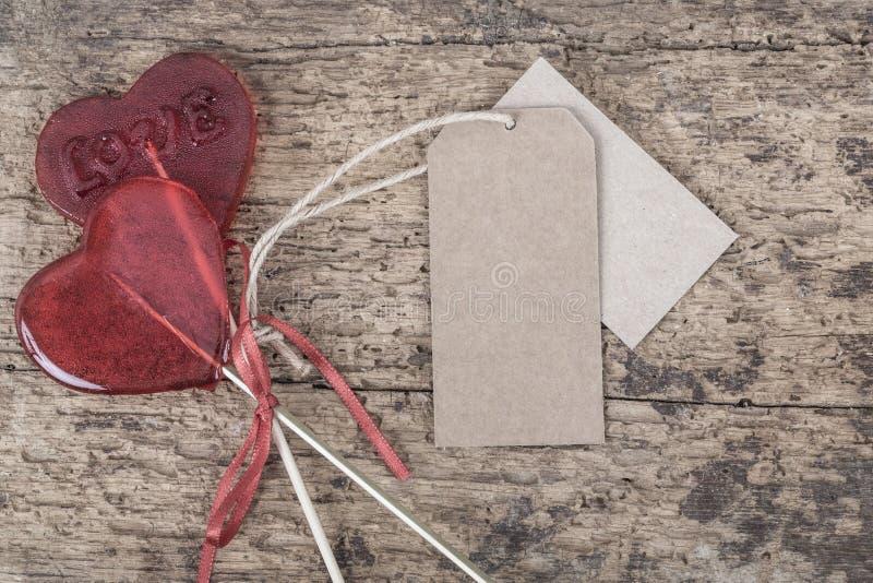 Herz formte rote Süßigkeiten auf Holztisch mit Aufklebern lizenzfreies stockfoto