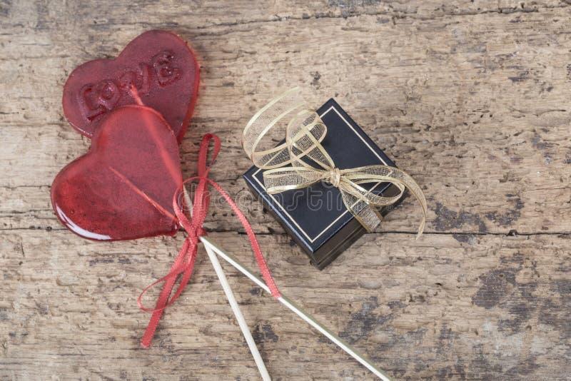 Herz formte rote Süßigkeiten und Geschenkbox auf hölzernem Hintergrund stockfotos