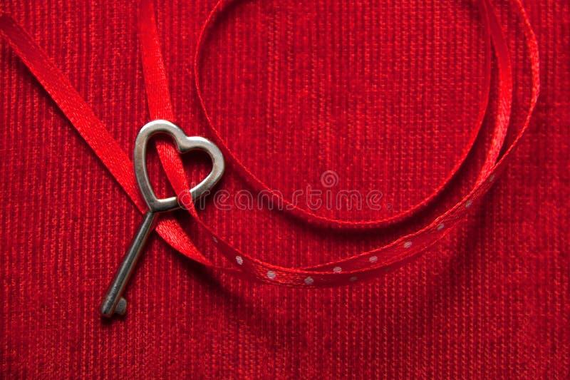 Herz formte Schlüssel- und rotes Band auf Samt lizenzfreie stockbilder