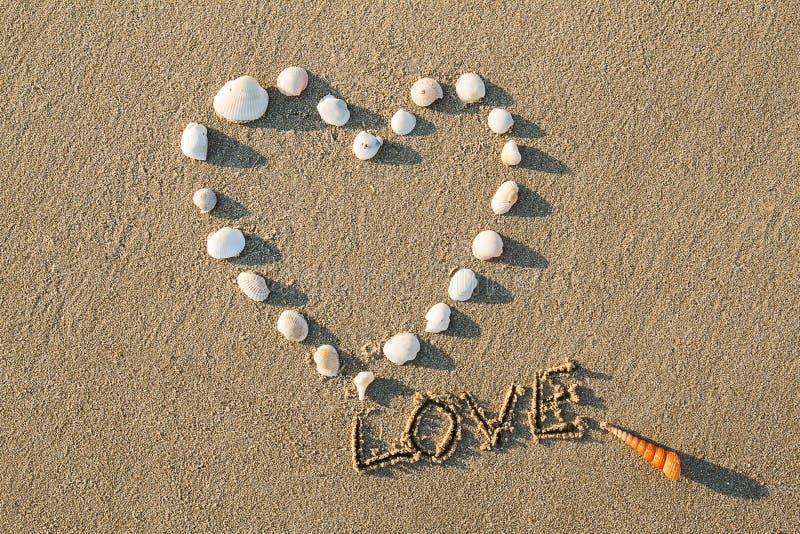 Herz formte Seeoberteile und Zeichnungsbuchstabeliebe auf dem Sandstrand lizenzfreie stockfotografie