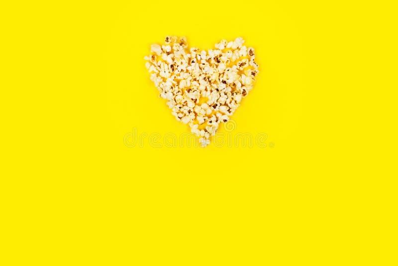 Herz formte weißes flaumiges Popcorn auf gelbem Hintergrund lizenzfreies stockbild