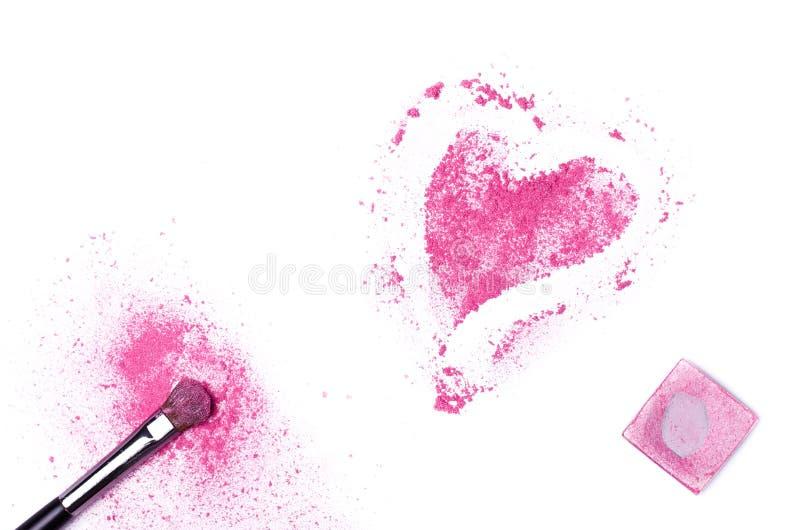 Herz formte zerquetschte Lidschatten mit der Bürste, die auf weißem BAC lokalisiert wurde stockfoto