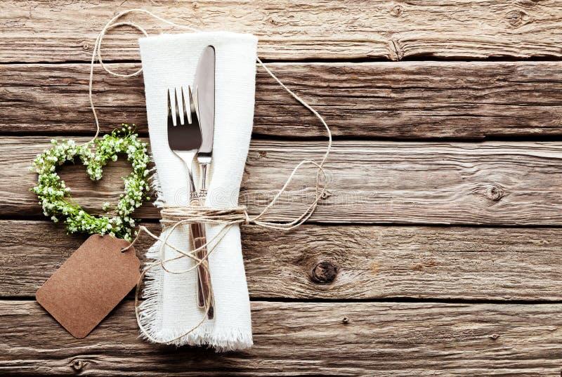 Herz geformter Hochzeits-Kranz am rustikalen Gedeck lizenzfreie stockfotos