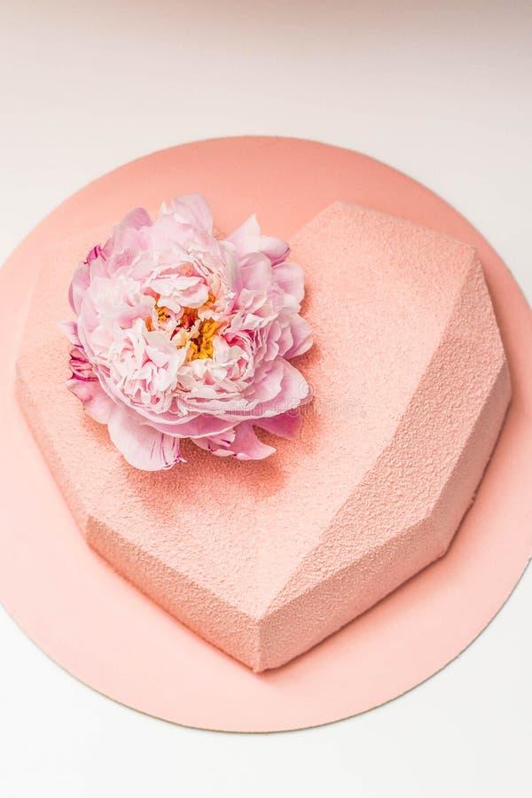 Herz geformter Kuchen verziert mit Pfingstrosenblume stockfotos