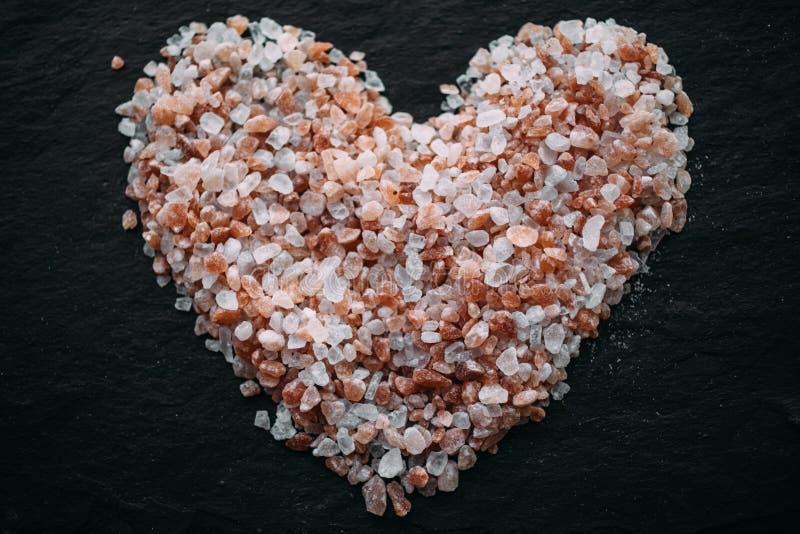 Herz gemacht vom Himalajasalz auf schwarzem Schiefer Beschneidungspfad eingeschlossen Herz formte Salz als Hintergrund lizenzfreie stockbilder