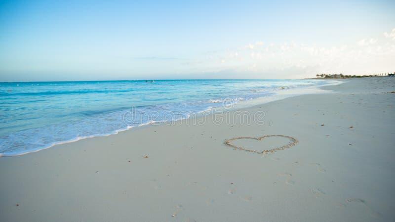 Herz gemalt im weißen Sand auf einem tropischen Strand lizenzfreie stockfotografie