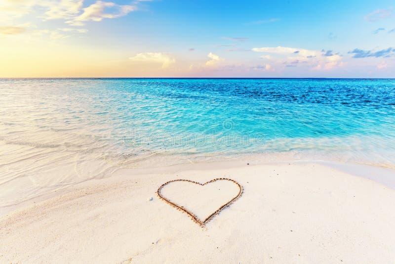 Herz gezeichnet auf Sand eines tropischen Strandes bei Sonnenuntergang stockbilder