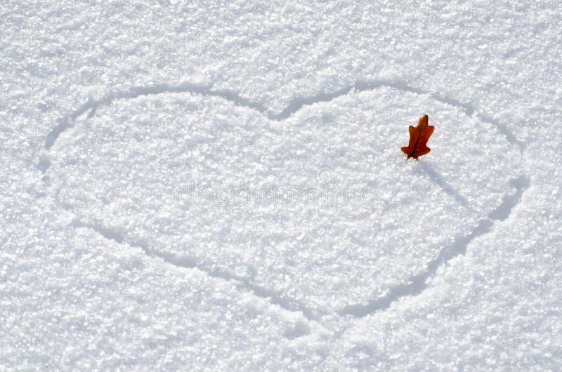Herz gezeichnet auf Schnee und Blatt, Valentinstagkonzept stockfoto
