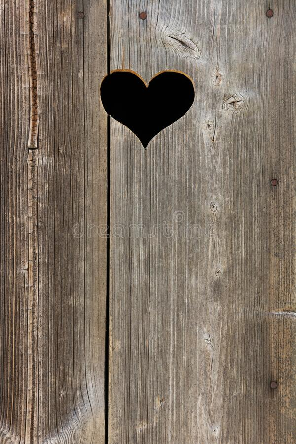A hole in heart shape in an old wooden door stock images