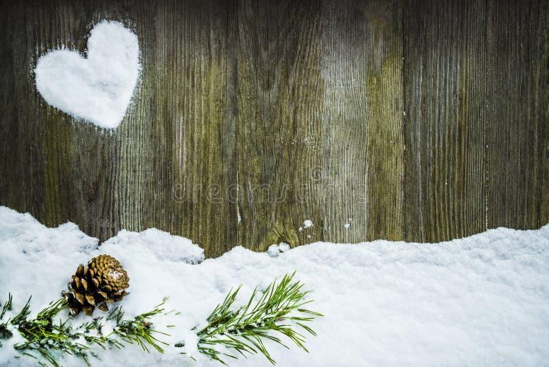 Herz machte vom Schnee auf einem hölzernen Hintergrund lizenzfreies stockbild
