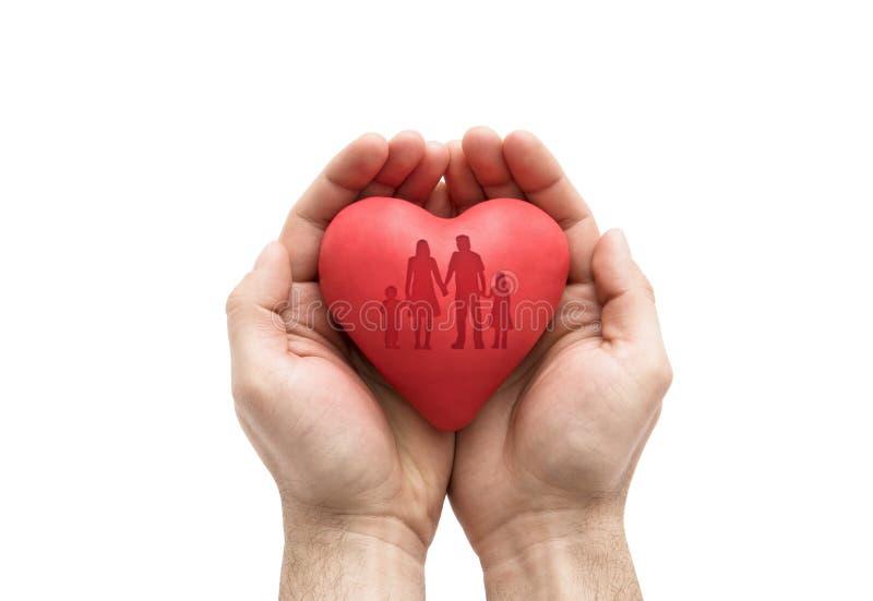 Herz mit aufgeprägter Familienform in Mann ` s Händen stockfoto