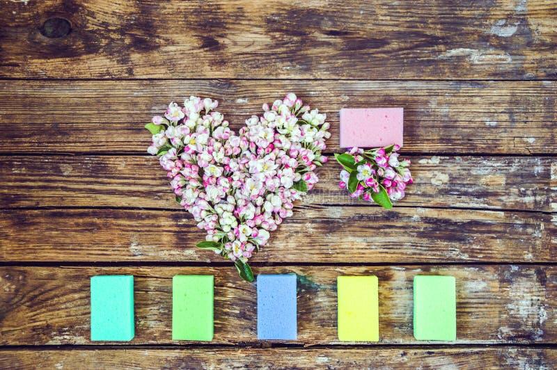 Herz von Blumen und von Knospen eines Apfelbaums, um mehrfarbige Waschlappen auf einem alten h?lzernen Hintergrund lizenzfreie stockbilder