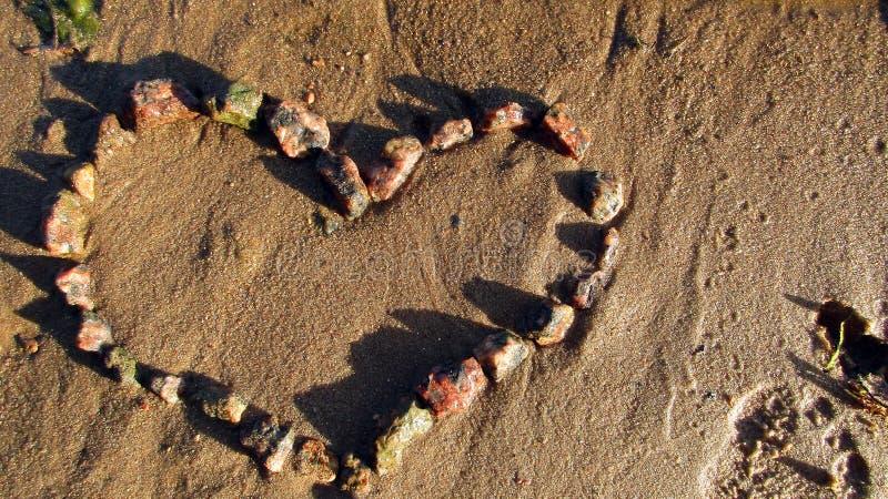 Herz von rötlichen Steinen auf dem sandigen Ufer stockfotos