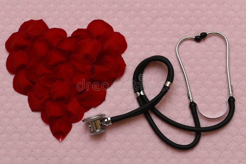 Herz von rosafarbenen Blumenblättern und von Stethoskop stockbild