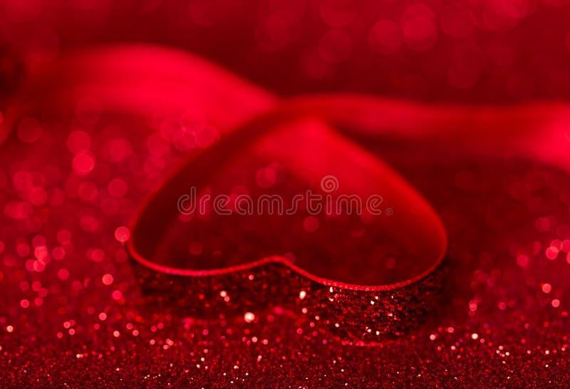 Herz wird mit hellem rotem Band auf glänzendem Hintergrund für Valentinstag gezeichnet lizenzfreies stockbild