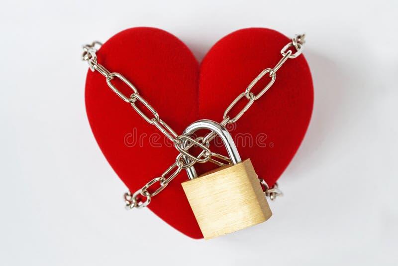 Herz zugeschlossen mit Kette und Vorhängeschloß auf weißem Hintergrund - Konzept der Liebe stockfoto