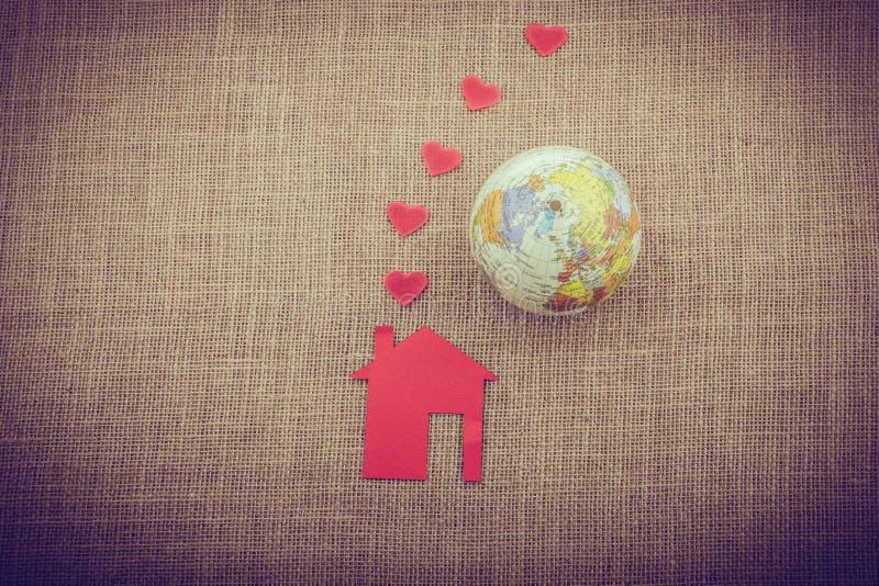 Herzen, die aus Kamin des Papierhauses neben einer Kugel herauskommen lizenzfreies stockbild