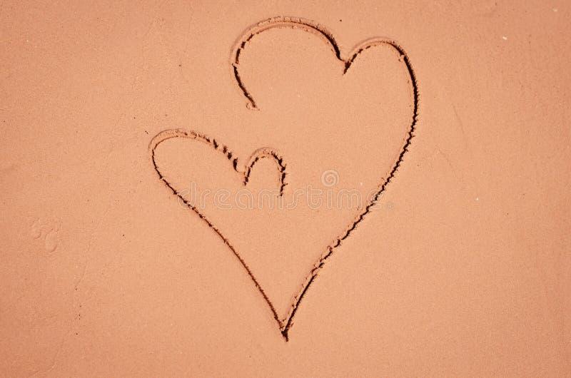 Herzen gezeichnet in Sand stockbild