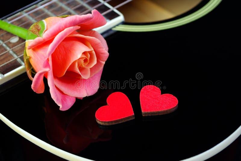 Herzen von Liebhabern, von schöner rosafarbener und schwarzer Akustikgitarre lizenzfreie stockfotos