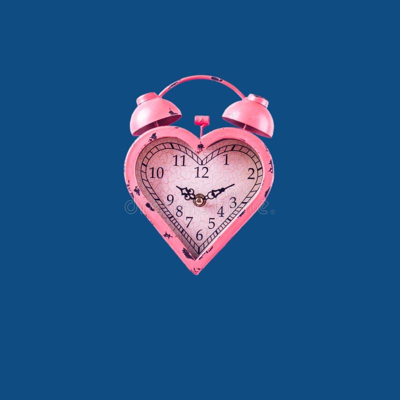 Herzförmige rosafarbene Uhr auf klassisch blauem Hintergrund Valentinstag- und Liebesfeindlichkeit und -dauer-Konzept stockfotos