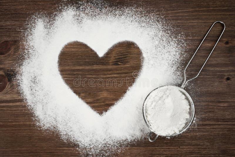 Herzform des Mehls auf braunem Hintergrund des hölzernen Brettes lizenzfreies stockfoto