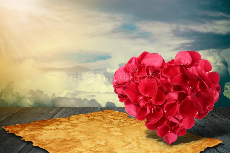 Herzform machte aus rosafarbenen Blumenbl?ttern mit altem Papier heraus auf h?lzerner Plattformtabelle stockfotos