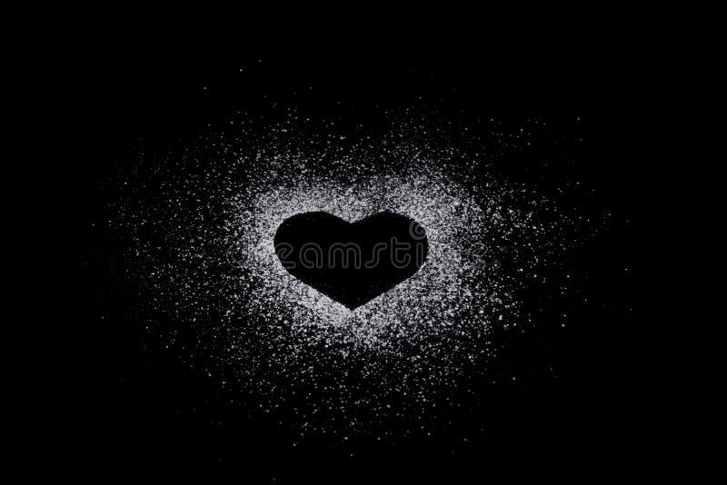 Herzform machte vom Puderzucker auf schwarzem totalhintergrund mit c lizenzfreies stockfoto
