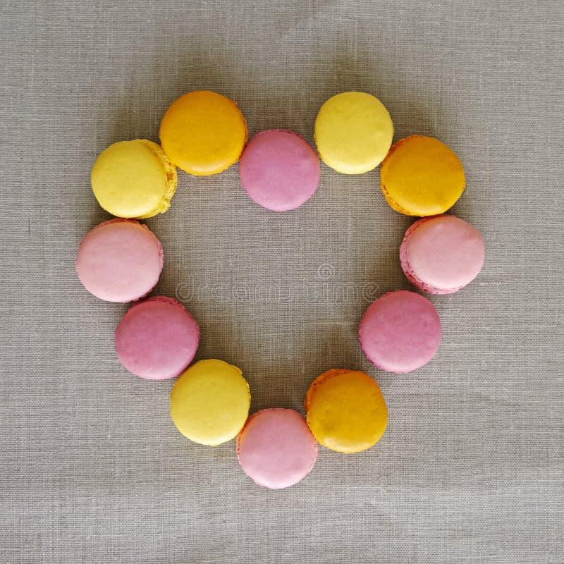 Herzform machte von den süßen bunten macarons Sortierte bunte köstliche französische macarons auf grauem Hintergrund S??e Nahrung lizenzfreies stockfoto