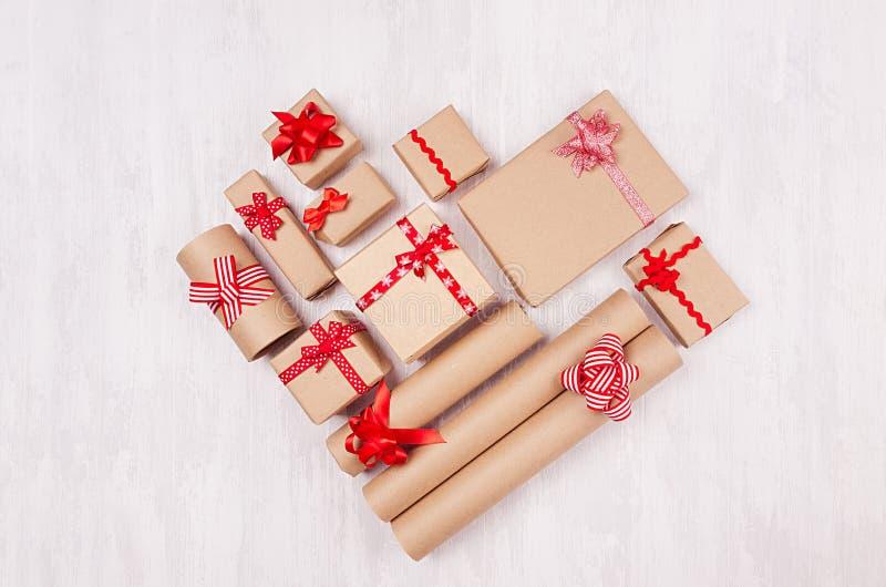 Herzform von Weihnachtsgeschenken von Kraftpapiergeschenken mit roten Bändern und von Bögen auf weichem hellem weißem hölzernem B lizenzfreies stockbild
