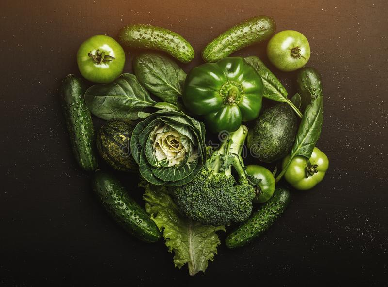 Herzformform durch verschiedenes grünes gesundes Gemüse, Draufsicht lizenzfreies stockfoto