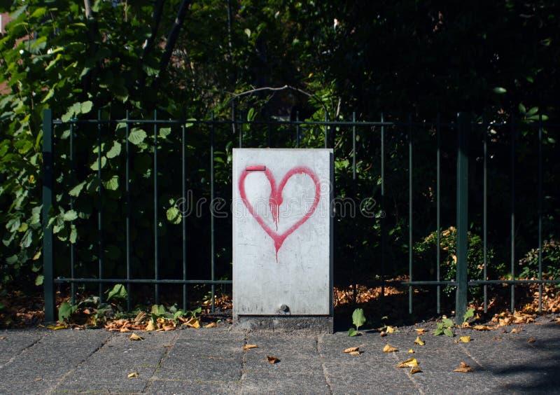 Herzgraffiti auf dem elektrischen Kasten in der Straße stockfotografie