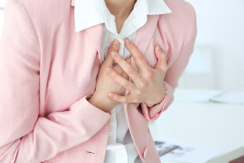 Herzinfarkt-Konzept Junge Frau, die unter Schmerz in der Brust leidet lizenzfreies stockbild