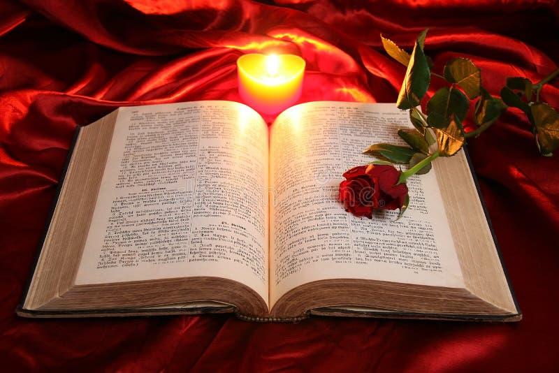Herzkerze auf offener Bibel und Rotrose lizenzfreie stockfotos