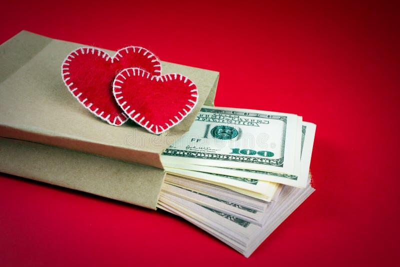 Herzpapiertüte mit Geld auf einem roten Hintergrund lizenzfreies stockbild