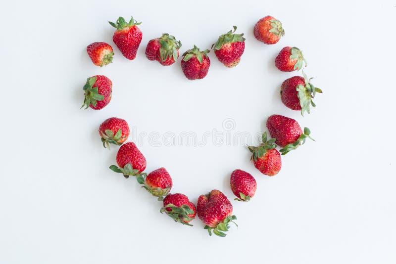 Herzrahmen gemacht von den Erdbeeren auf weißem Hintergrund Flache Lage, Draufsicht, Kopienraum, zentriert lizenzfreie stockfotos