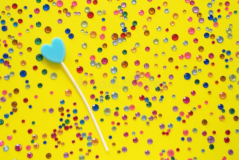 Herzsüßigkeit Lutscher der blauen Farbe auf einem gelben Hintergrund mit mehrfarbigen Bergkristallen Süßer Hintergrund stockbilder