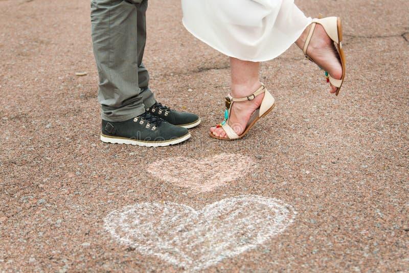 Herzsymbole formten mit Zeichenstiften auf dem Boden und zwei Leuten im lo lizenzfreie stockfotos