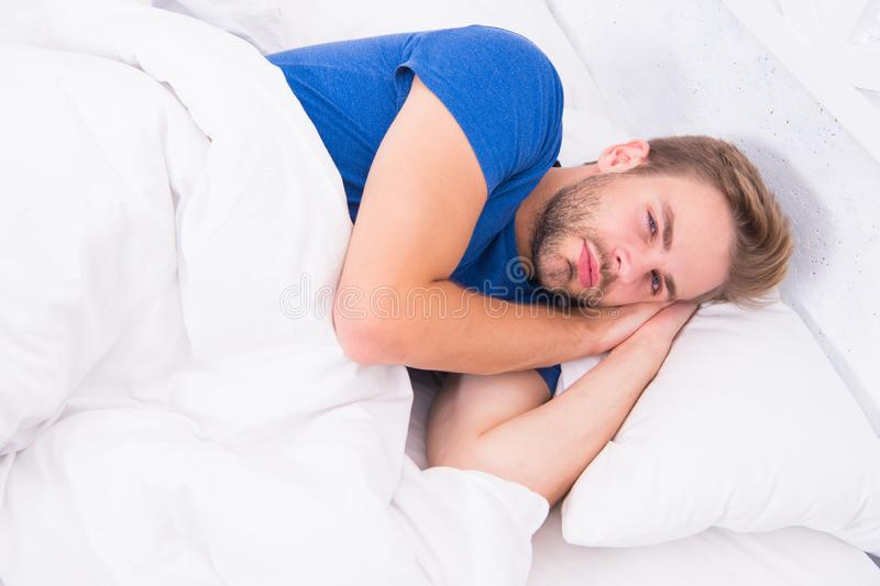 Hes too lazy to get up. Lazy man lying in bed. Handsome man after waking up in lazy morning. Being a little lazy stock images