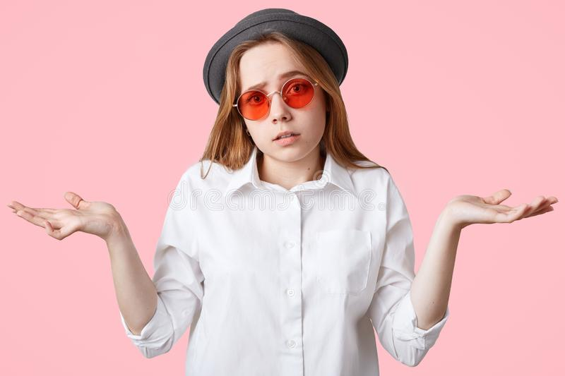 Hesitant beautiful hipster female shrugs shoulders in bewilderment, being uncertain and has clueless expression, wears stylish hat. And red sunglasses, poses stock images