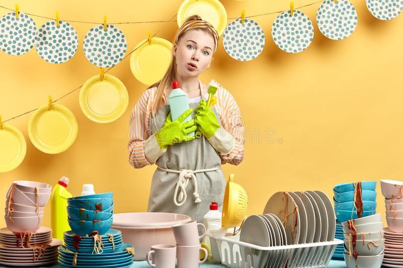 Hesitant displeased surprised girl holds brush and cleaning liquid stock images