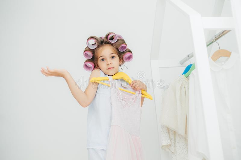 Hesitant girl with clueless expression, doesn`t know what to wear, holds hangers with dress, has curlers on head, isolated over wh. Ite background. Cute child stock photography