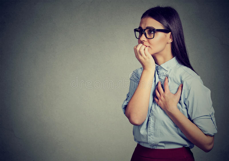 Hesitant woman biting her fingernails craving for something or anxious. Closeup portrait unsure hesitant woman biting her fingernails craving for something or stock images